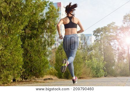A running girl) a girl running along the pathway the background of high-rise buildings