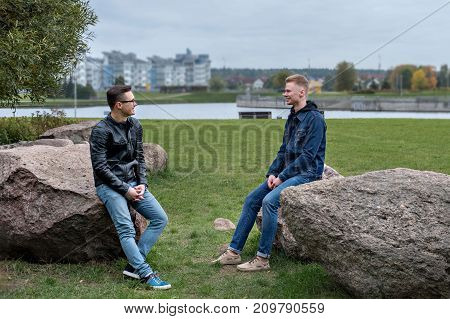 two guys students sitting and talking, city landscapes and buildings in the background