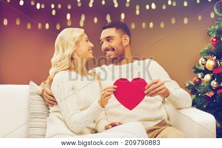 christmas, holidays, love and people concept - happy couple with red heart over lights background