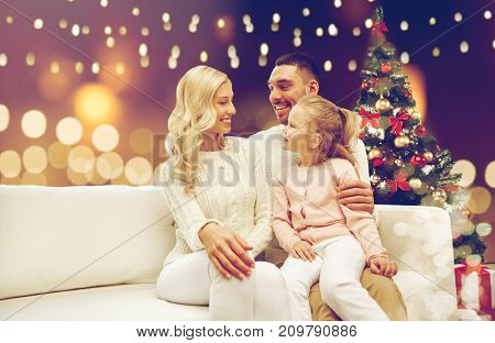 family, holidays and people concept - happy mother, father and little daughter sitting on sofa at christmas tree over lights background