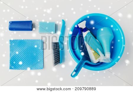 housework, housekeeping and household concept - basin with cleaning stuff on white background over snow