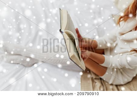 christmas, comfort, leisure and people concept - close up of happy young woman reading book at home over snow