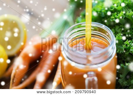 healthy eating, diet and vegetarian concept - close up of glass jug or mug with carrot juice and straw over snow