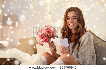 holidays, winter, birthday and people concept - happy young woman with flowers reading greeting card in bed at home bedroom over snow
