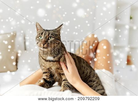 pets, comfort, winter and people concept - young woman with cat lying in bed at home over snow