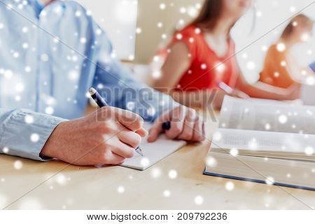 education, learning and people concept - close up of student hands with pen, notebook and book writing school test over snow