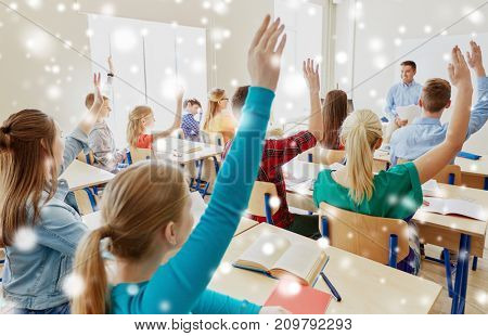 education, school and people concept - group of students raising hands and teacher with papers or tests over snow