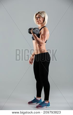 Full length portrait of a focused muscular sportswoman working out with a heavy dumbbell isolated over gray background