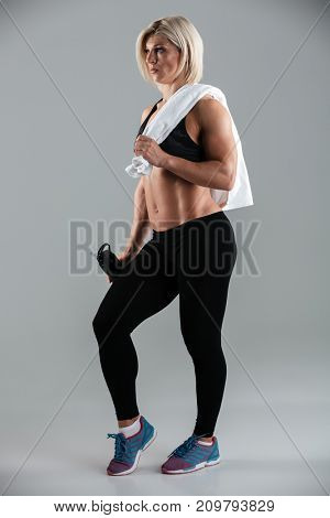 Full length portrait of a fit muscular adult sportswoman holding water bottle and a towel while standing isolated over gray background
