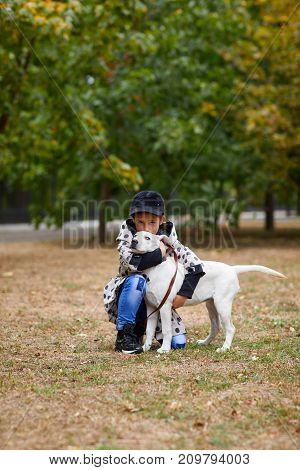 Funny doggie walking with owner in the park. Pet with girl outdoors on a natural background. Animal concept.