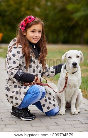 Cute girl kid with doggie walking in the park. Having fun together outdoors on the nature background. Close-up of pet with owner. Animal concept.