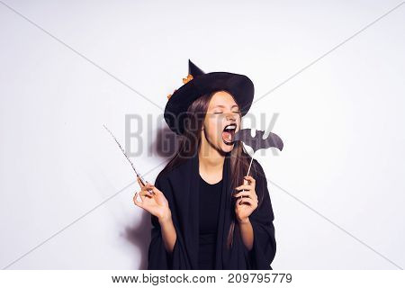 girl in a witch costume tries to bite a bat
