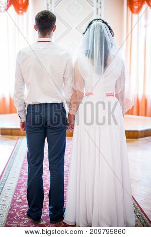 newlyweds are holding hands rear view. Vertical frame