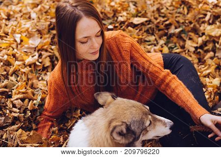 girl lies in a park in fallen leaves with her dog
