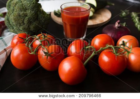 ripe red tomatoes are lying on a black stylish table. in the background we see a glass of tomato juice, red onions, broccoli and green squash on a wooden cutting board. Perfect match