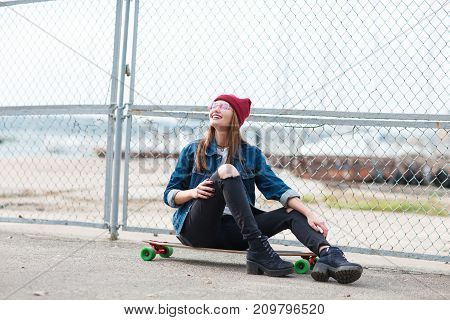 Beautiful young girl in a jeans jacket with glasses and a red cup sitting on skateboard and posing on camera on the nature background. Close-up of girl.