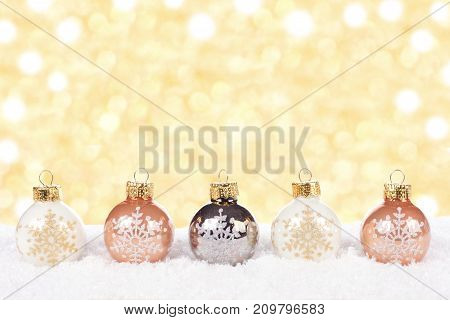 White And Gold Christmas Ornaments In Snow With Twinkling Gold Background