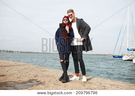 Handsome man and pretty girl in love. Happy couple smiling and laughing on the street. River on the background. Full length of couple.
