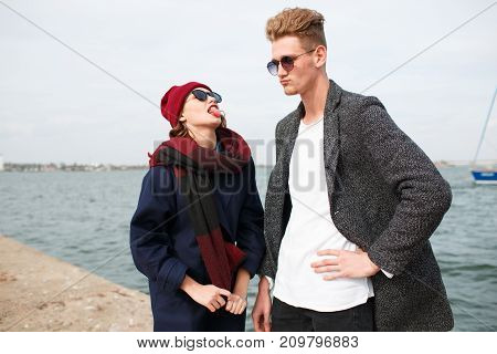 Handsome man and pretty girl in love. Happy couple smiling and laughing on the street. River on the background. Close-up of couple.