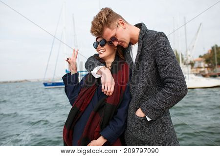 Happy couple in love hugging. Pretty girl in glasses and attractive man smiling and laughing outdoors. River on the background. Close-up of couple.
