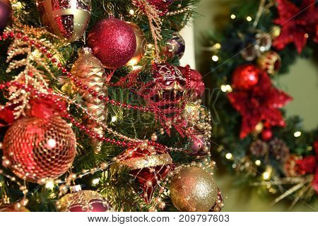 Detail of Christmas tree with poinsettia wreath in background