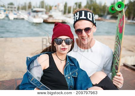 Happy couple in love hugging. Pretty girl in a red cup and attractive man holds skateboard. Smiling and laughing outdoors. River on the background. Close-up of couple.