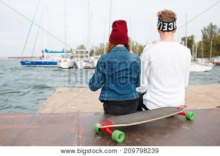 Happy couple in love hugging. Pretty girl in a red cup and attractive man sitting near a skateboard. Smiling and laughing outdoors. River on the background. Close-up of couple.