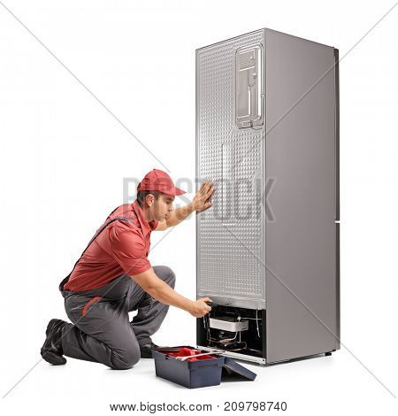 Young repairman fixing a refrigerator isolated on white background