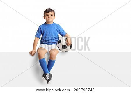 Little footballer sitting on a panel and looking at the camera isolated on white background