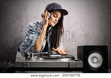 Female DJ playing music on a turntable against a rusty gray wall