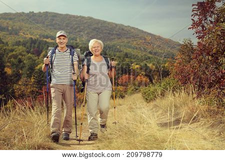 Full length portrait of two elderly hikers walking towards the camera outdoors