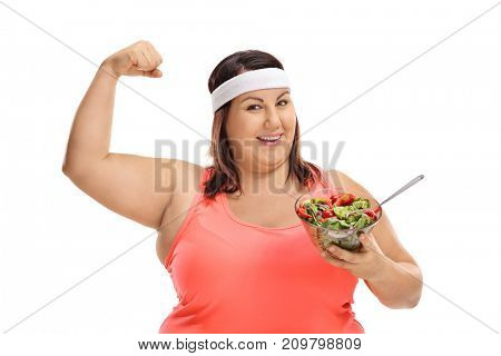 Overweight woman holding a salad and flexing her bicep isolated on white background