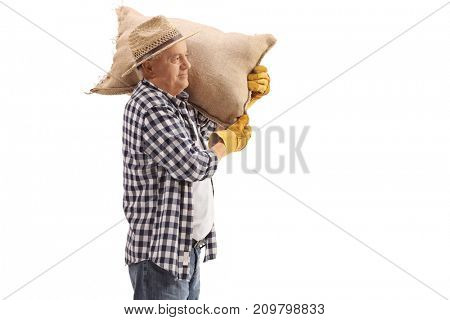 Mature farmer holding a burlap sack on his shoulder isolated on white background