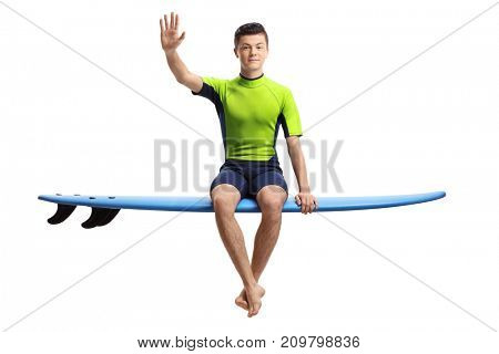 Teenage surfer sitting on a surfboard and waving at the camera isolated on white background