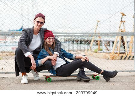 Pretty girl in a red cup sitting on a skateboard and handsome boy hugging a girl on the nature background. Copy space. Close-up of friends.