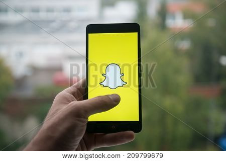 London, United Kingdom, october 3, 2017: Man holding smartphone with Snapchat logo with the finger on the screen