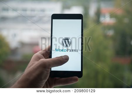 London, United Kingdom, october 3, 2017: Wordpress Man holding smartphone with  logo with the finger on the screen