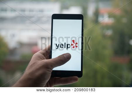 London, United Kingdom, october 3, 2017: Yelp Man holding smartphone with  logo with the finger on the screen