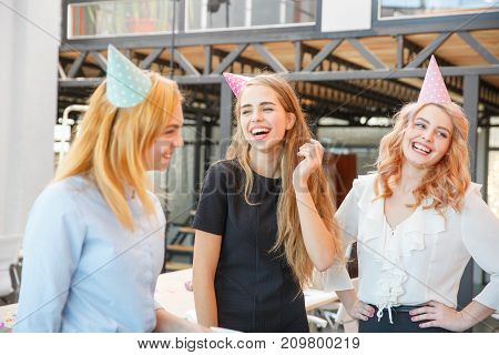 Girls in the office celebrate the holiday on a weekday working day, all smart and beautiful