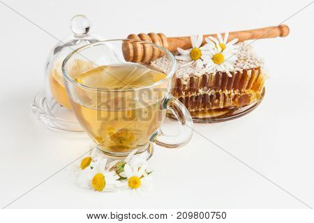 Honeycomb and chamomile tea on white
