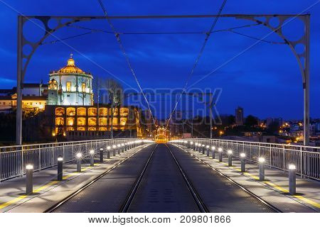 Empty tram rails on the Dom Luis I or Luiz I iron arch bridge across Douro river and Monastery of Serra of Pilar in Porto during morning blue hour, Portugal.