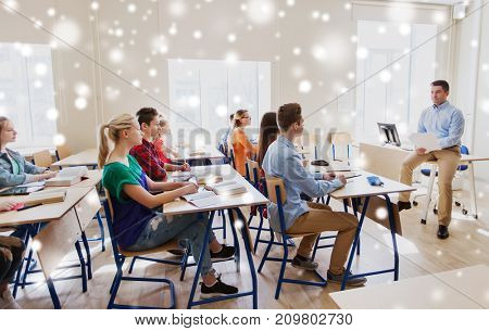 education, school and people concept - group of happy students and teacher with papers or tests over snow