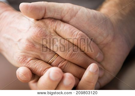 relationships, marriage and old people concept - close up of senior couple holding hands