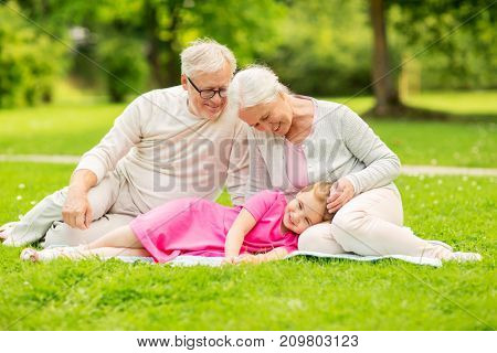 family, generation and people concept - happy smiling grandmother, grandfather and little granddaughter resting on blanket at park