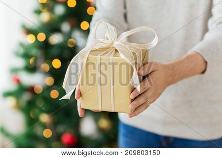 christmas, holidays and people concept - close up of man with gift box at home
