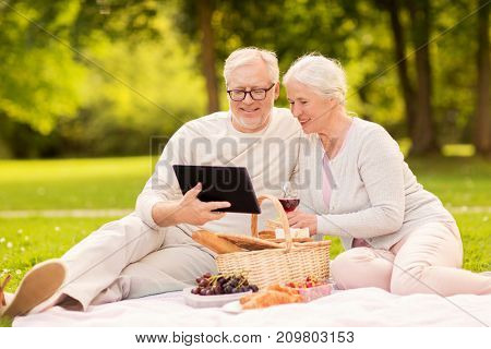old age, holidays, leisure and people concept - happy senior couple with picnic basket sitting on blanket at summer park