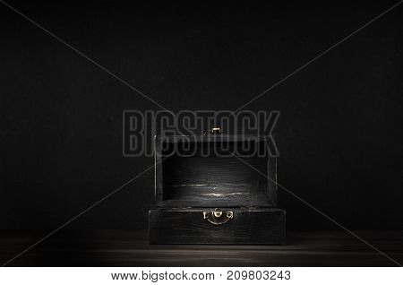 Old Dark Wooden Treasure Chest With Opened Lid On Black Background