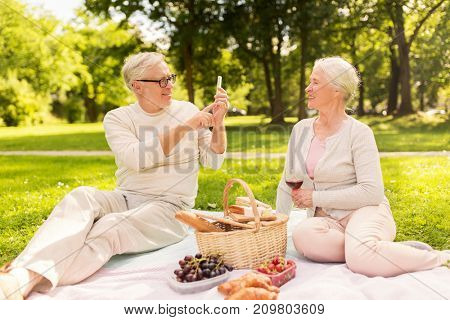 old age, leisure and people concept - happy senior couple with picnic basket and wine taking picture by smartphone at summer park