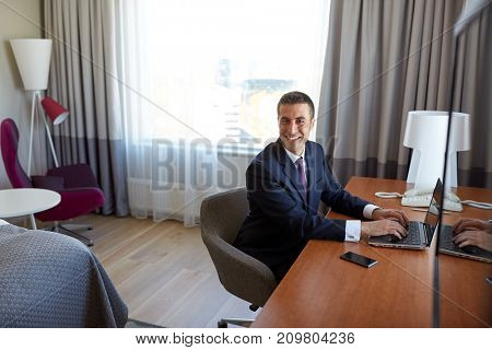 business trip, people and technology concept - businessman typing on laptop at hotel room