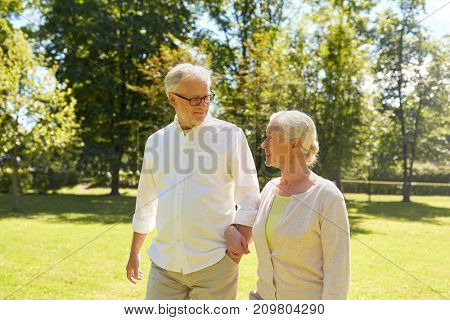old age, relationship and people concept - happy senior couple walking at summer city park